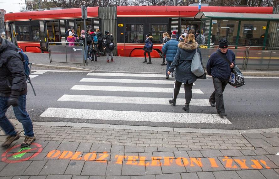 """Po tragicznych wypadkach, do których doszło na skutek zaaferowania smartfonem, władze Katowic i policja organizują akcję: """"Odłóż telefon i żyj""""."""